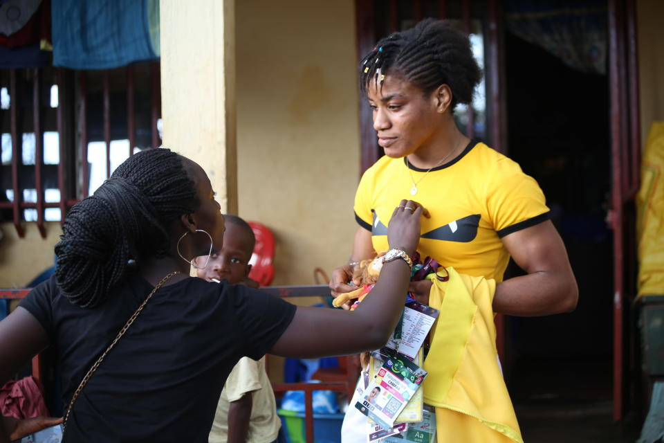 Guinean wrestler Fatoumata Yarie Camara, right, holding past credentials and medals, is greeted at her house in Conakry, Guinea, Monday July 19, 2021. A West African wrestler's dream of competing in the Olympics has come down to a plane ticket. Fatoumata Yarie Camara is the only Guinean athlete to qualify for these Games. She was ready for Tokyo, but confusion over travel reigned for weeks. The 25-year-old and her family can't afford it. Guinean officials promised a ticket, but at the last minute announced a withdrawal from the Olympics over COVID-19 concerns. Under international pressure, Guinea reversed its decision. (AP Photo/Youssouf Bah)