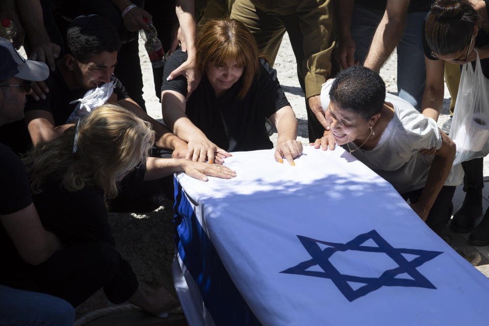 Relatives of Israeli soldier Omer Tabib, 21, mourn during his funeral at the cemetery in the northern Israeli town of Elyakim, Thursday, May 13, 2021. The Israeli army confirmed that Tabib was killed in an anti-tank missile attack near the Gaza Strip, the first Israeli military death in the current fighting between Israelis and Palestinians. (AP Photo/Sebastian Scheiner)