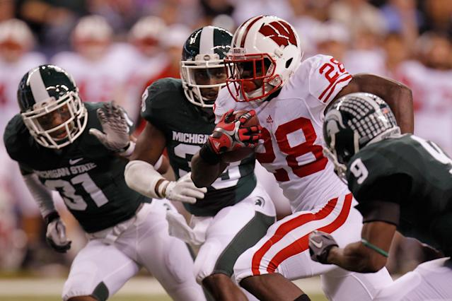 INDIANAPOLIS, IN - DECEMBER 03: Montee Ball #28 of the Wisconsin Badgers scores his second 6-yard rushing touchdown in the first quarter against Isaiah Lewis #9 of the Michigan State Spartans during the Big 10 Conference Championship Game at Lucas Oil Stadium on December 3, 2011 in Indianapolis, Indiana. (Photo by Gregory Shamus/Getty Images)
