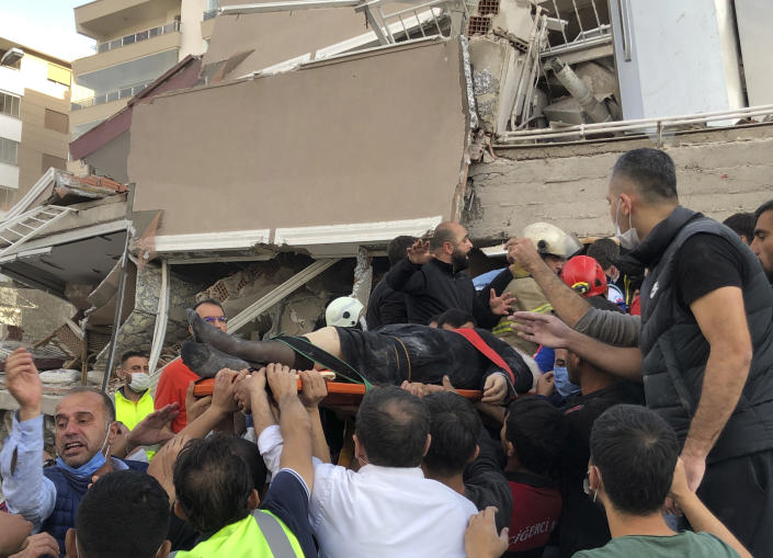 Rescue workers and local people carry a wounded person found in the debris of a collapsed building, in Izmir, Turkey, Friday, Oct. 30, 2020, after a strong earthquake in the Aegean Sea has shaken Turkey and Greece. Turkey's Disaster and Emergency Management Presidency said Friday's earthquake was centered in the Aegean at a depth of 16,5 kilometers (10.3 miles) and registered at a 6.6 magnitude. (AP Photo/Ismail Gokmen)
