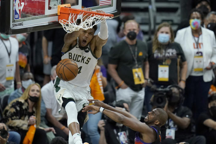 Milwaukee Bucks forward Giannis Antetokounmpo, top, dunks over Phoenix Suns guard Chris Paul during the second half of Game 5 of basketball's NBA Finals, Saturday, July 17, 2021, in Phoenix. (AP Photo/Ross D. Franklin)