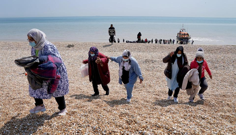 People thought to be migrants make their way up the beach at Dungeness in Kent after arriving on a small boat (Gareth Fuller/PA) (PA Wire)
