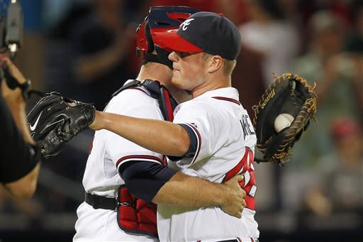 Atlanta Braves relief pitcher Craig Kimbrel, right, embraces catcher Brian McCann after the final out in the Braves' 5-4 win over the St. Louis Cardinals in a baseball game, Tuesday, May 29, 2012, in Atlanta. (AP Photo/John Bazemore)