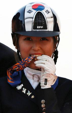 FILE PHOTO: South Korea's Chung Yoo-ra poses after winning the equestrian Dressage Team competition during the 17th Asian Games in Incheon