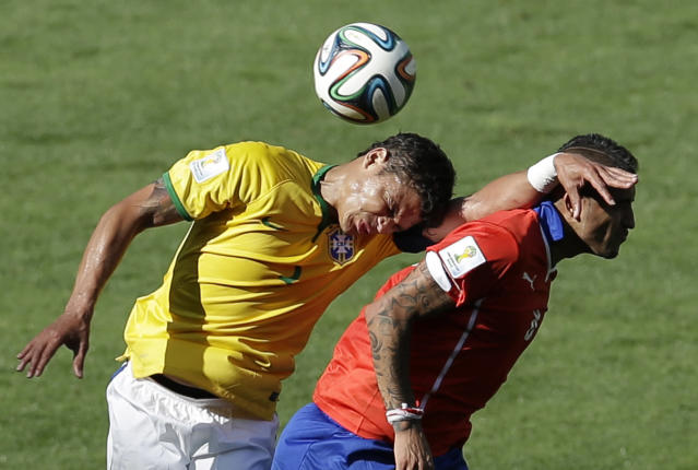 Brazil's Thiago Silva, left, and Chile's Arturo Vidal go for a header during the World Cup round of 16 soccer match between Brazil and Chile at the Mineirao Stadium in Belo Horizonte, Brazil, Saturday, June 28, 2014. (AP Photo/Hassan Ammar)