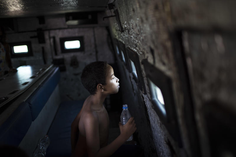"""A young resident looks through a small bullet proof window as he sits inside a police armored vehicle after a police operation to occupy the Vila Pinheiro, part of the Mare slum complex in Rio de Janeiro, Brazil, Sunday, March 30, 2014. The Mare complex of slums, home to about 130,000 people and located near the international airport, is the latest area targeted for the government's """"pacification"""" program, which sees officers move in, push out drug gangs and set up permanent police posts. (AP Photo/Felipe Dana)"""