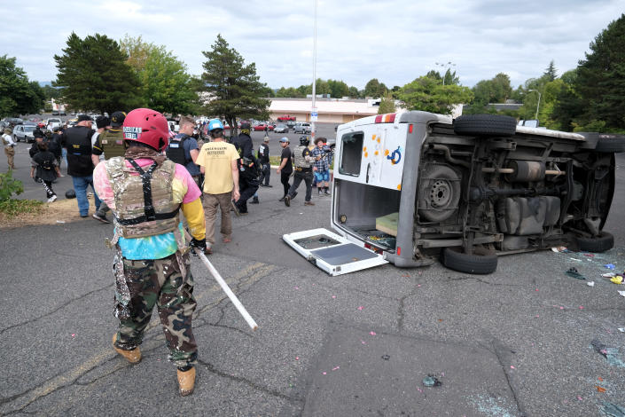 A van that was driven by anti-fascist protesters is pictured flipped on its side with all windows smashed after it was attacked for trying to drive into a Proud Boys rally Sunday, Aug. 22, 2021, in Portland, Ore. (AP Photo/Alex Milan Tracy)