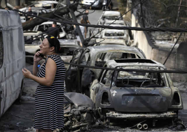 <p>A woman reacts as she stands amid the charred remains of burned-out cars in Mati east of Athens, Tuesday, July 24, 2018. (Photo: Thanassis Stavrakis/AP) </p>