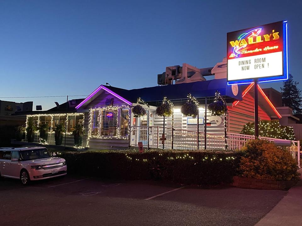 A restaurant decorated in lights advertises on a signboard that its dining room is open.
