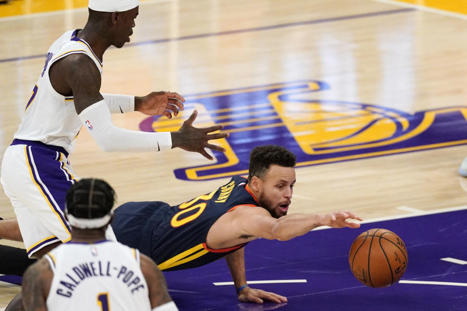 Golden State Warriors guard Stephen Curry, right, dives for a loose ball while Los Angeles Lakers guard Dennis Schroder, left, and guard Kentavious Caldwell-Pope watch during the first half of an NBA basketball game Sunday, Feb. 28, 2021, in Los Angeles. (AP Photo/Mark J. Terrill)