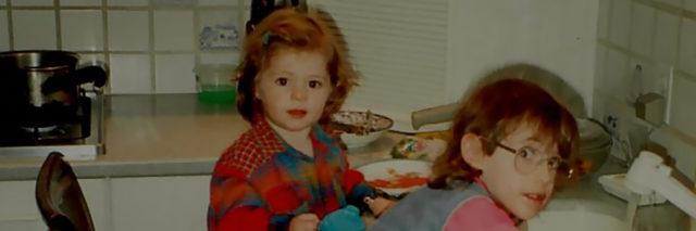 Sarah as a child leaning against the sink washing dishes with her sister.