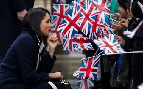 Meghan Markle kneels as he chats to flag-waving children  - Credit: Heathcliff O'Malley for The Telegraph