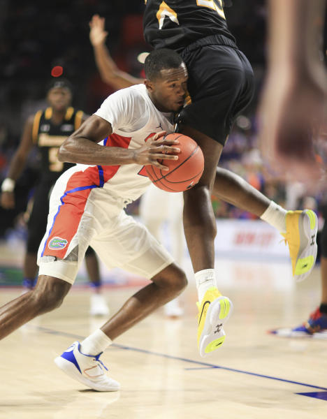 Florida guard Scottie Lewis, left, is fouled by Towson guard Brian Fobbs, right, during the second half of an NCAA college basketball game Thursday, Nov. 14, 2019, in Gainesville, Fla. (AP Photo/Matt Stamey)