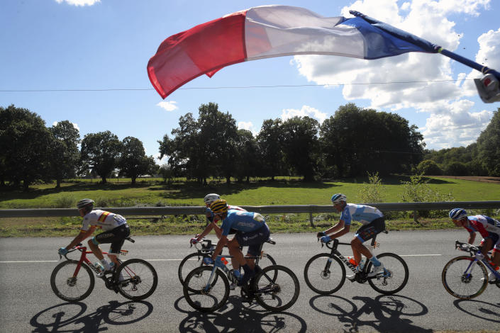 FILE - In this Sept.10, 2020 file photo, a French flag flies over riders in a breakeway during the stage 12 of the Tour de France cycling race over 218 kilometers from Chauvigny to Sarran. (AP Photo/Thibault Camus, File)