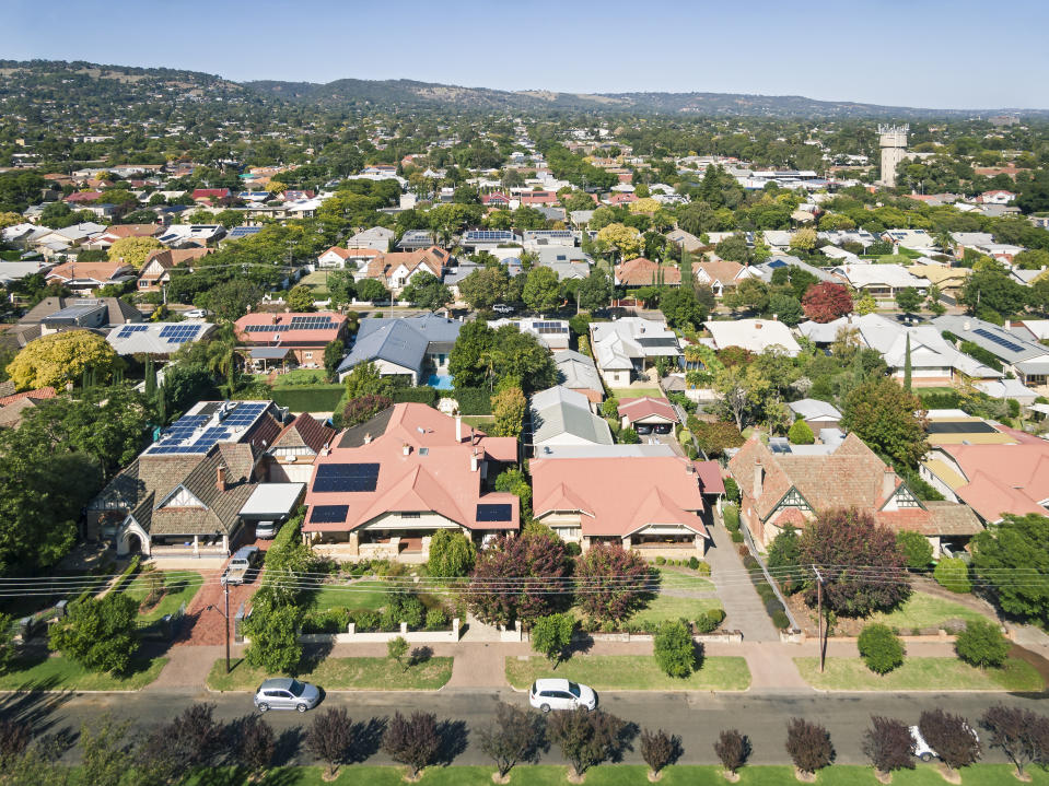 Elevated view of houses & rooftops in leafy eastern suburb of Adelaide during the transition from summer to autumn: sunny with autumn leaf colours. Note the many solar panels installed on the rooftops providing power generation for the city.