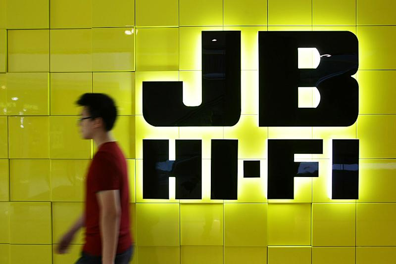 A man walks past a JB Hi-Fi Ltd. logo displayed outside a store in Sydney, Australia, on Monday, Feb. 13, 2012. JB Hi-Fi is Australia's second-largest electrical retailer. Photographer: Brendon Thorne/Bloomberg via Getty Images