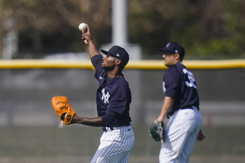 New York Yankees' Domingo German, left, warms up during a spring training baseball workout Monday, Feb. 22, 2021, in Tampa, Fla. (AP Photo/Frank Franklin II)