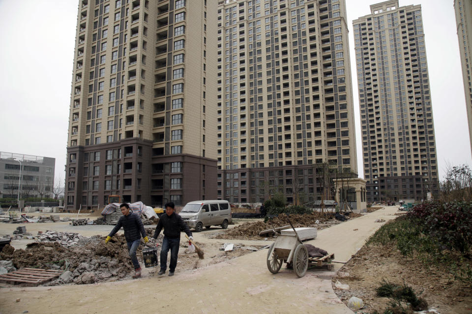 In this photo taken Friday, March 17, 2017, workers labor at a newly built condominium complex where a controversial mosque is planned in Hefei in central China's Anhui province. On the dusty plains of the Chinese heartland, the bitter fight over the mosque illustrates how a surge in anti-Muslim sentiment online is spilling over into the real world. If left unchecked, scholars say, such attitudes risk inflaming simmering ethnic tensions that have in past erupted in bloodshed. (AP Photo/Gerry Shih)
