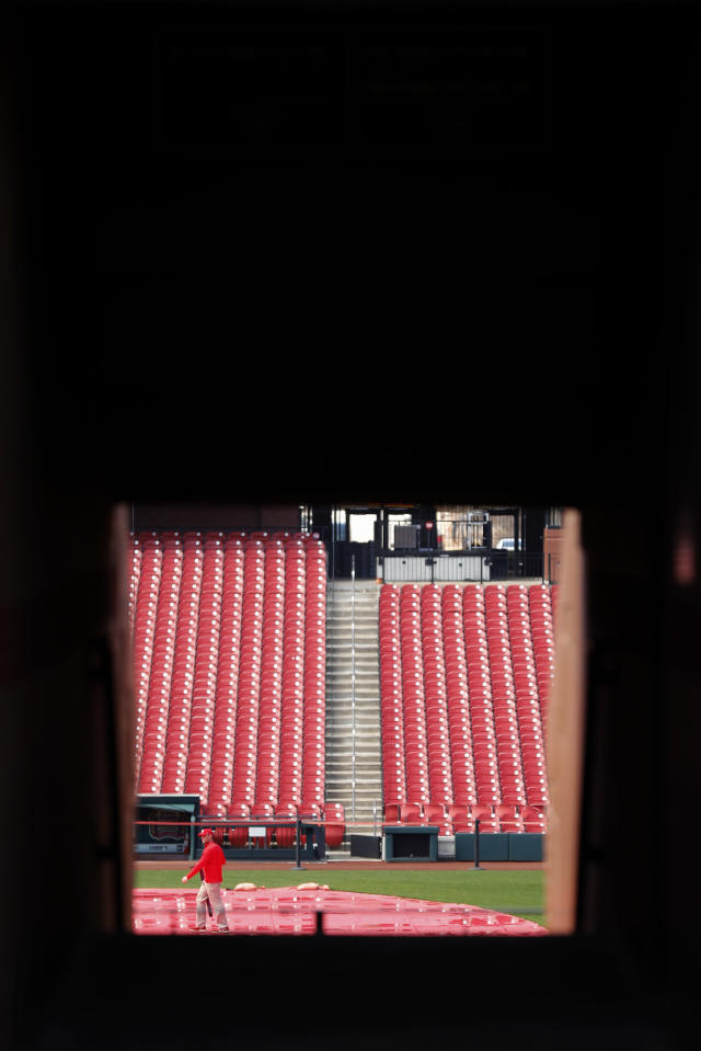 A grounds crew member walks on the field inside Busch Stadium, home of the St. Louis Cardinals baseball team, Wednesday, March 25, 2020, in St. Louis. The start of the regular season, which was set to start on Thursday, is on hold indefinitely because of the coronavirus pandemic. (AP Photo/Jeff Roberson)