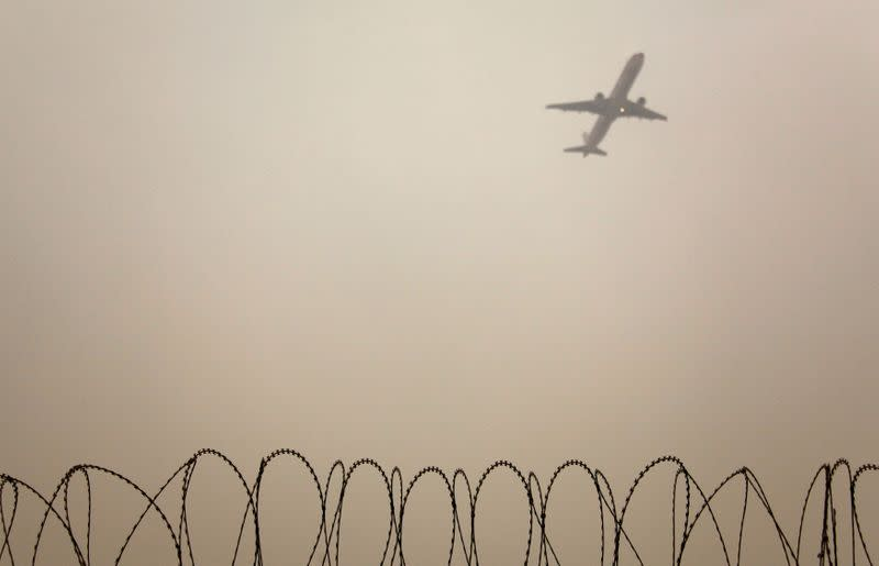 FILE PHOTO: A plane flies in the polluted air in Beijing