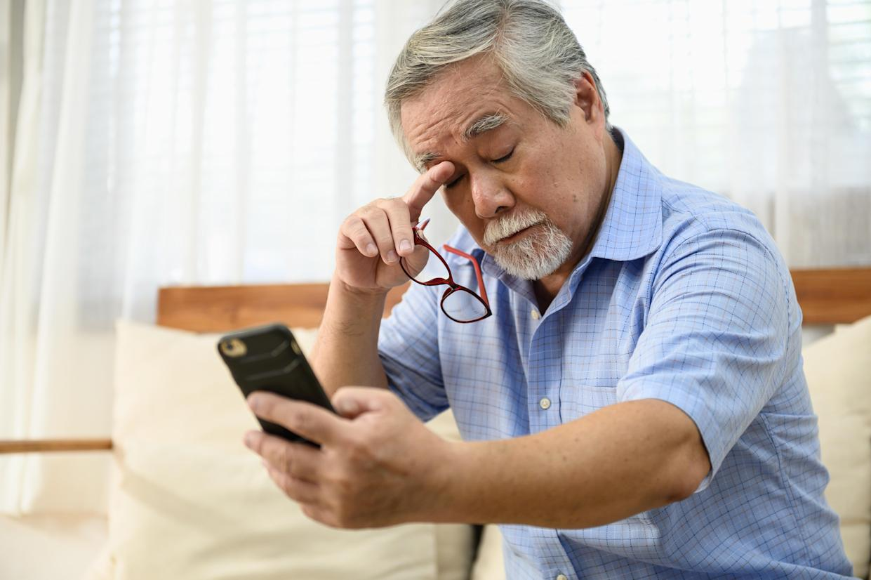 A man looking tired looking at his phone