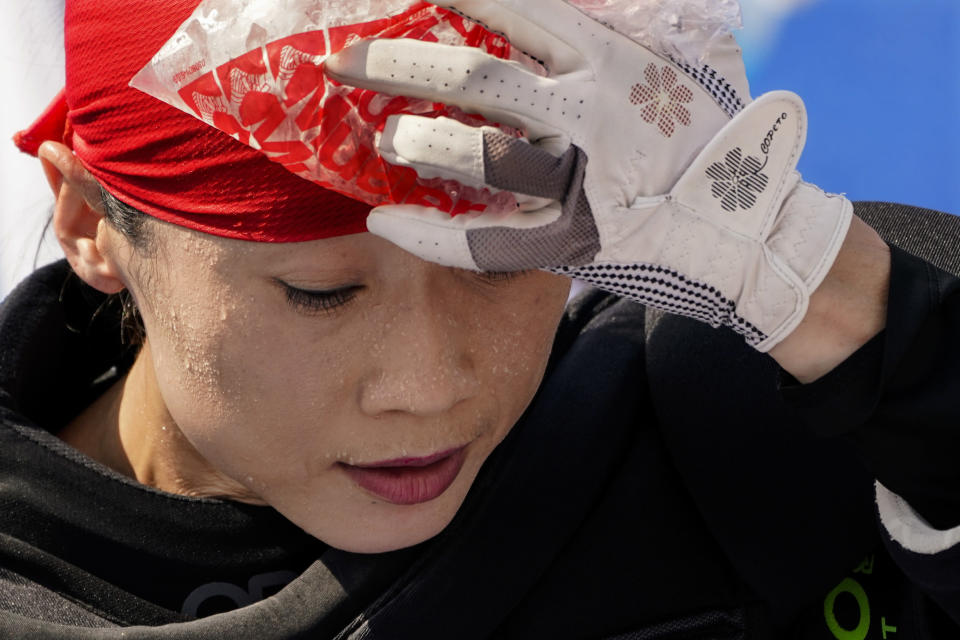 Beads of sweat gather on the face of China women's field hockey goalkeeper Dongxiao Li as she presses a bag of ice against her head during practice hours at the 2020 Summer Olympics, Friday, July 23, 2021, in Tokyo, Japan. (AP Photo/John Minchillo)