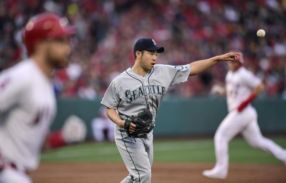 Seattle Mariners starting pitcher Yusei Kikuchi, of Japan, center, throws out Los Angeles Angels' Jonathan Lucroy, left, at first as Mike Trout runs to third during the first inning of a baseball game Saturday, April 20, 2019, in Anaheim, Calif. (AP Photo/Mark J. Terrill)