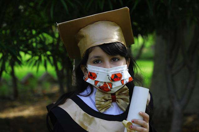 A girl wears a mask during a photo session to celebrate the end of the school year in Gaza City. (Getty Images)