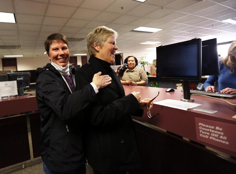 Kody Partridge, left, and Laurie Wood celebrate while applying for a marriage license at the Salt Lake County Clerk's Office in Salt Lake City on Friday, Dec. 20, 2013. The couple were plaintiffs in a case where a federal judge ruled on Friday that Utah's ban on same-sex marriage is unconstitutional. (AP Photo/Kim Raff)