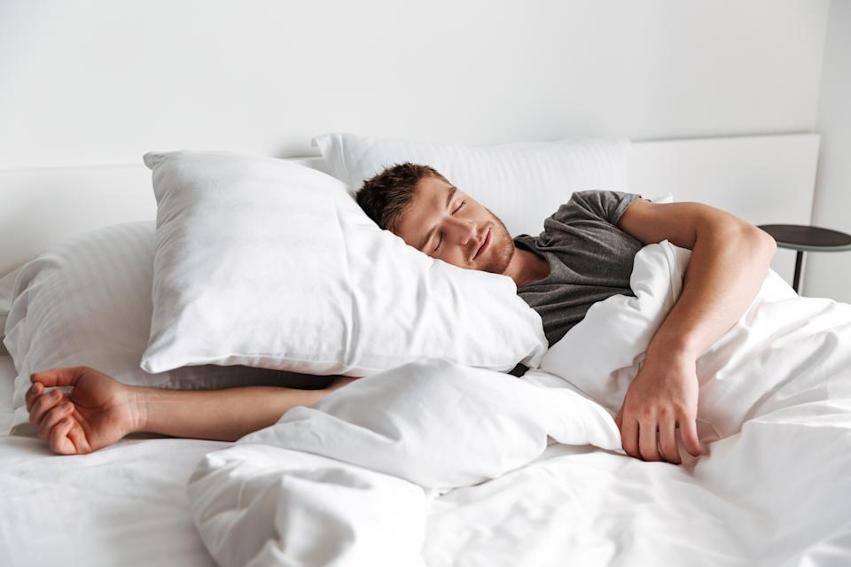 Attractive young man sleeping in bed at home