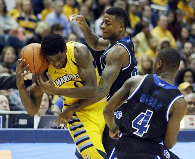Marquette's Jamil Wilson, left, is fouled as he tries to drive past Seton Hall's Sterling Gibbs (4) and Fuquan Edwin during the first half of an NCAA college basketball game Saturday, Jan. 11, 2014, in Milwaukee. (AP Photo/Morry Gash)