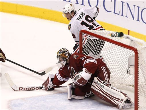 Phoenix Coyotes' Mike Smith, bottom, makes a save on a shot by Chicago Blackhawks' Jonathan Toews (19) during the first period in Game 5 of an NHL hockey Stanley Cup first-round playoff series Saturday, April 21, 2012, in Glendale, Ariz.AP Photo/Ross D. Franklin)