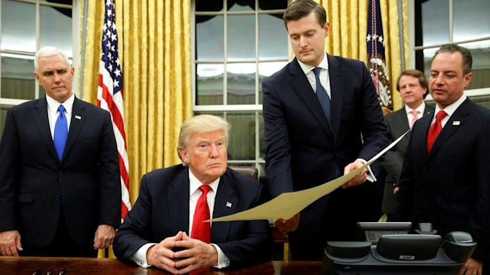 Rob Porter, pictured holding the document for President Trump, was accused of abuse by his two ex-wives