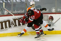 New Jersey Devils left wing Miles Wood (44) checks Philadelphia Flyers left wing Samuel Morin (55) against the boards during the first period of an NHL hockey game Thursday, April 29, 2021, in Newark, N.J. (AP Photo/Kathy Willens)