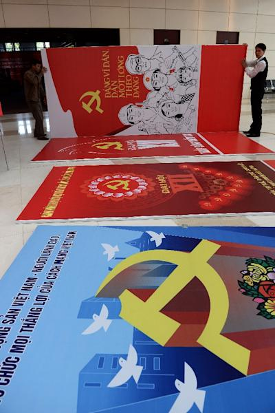 Workers set up posters and decorations at the My Dinh National Convention Center, the main venue of the upcoming Vietnam Communist Party's 12th National Congress, in Hanoi, on January 18, 2016 (AFP Photo/Hoang Dinh Nam)