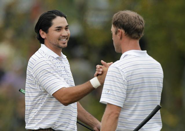 International's Jason Day, left, of Australia, shakes hands with teammate Graham DeLaet after winning their match against United States' Steve Stricker and Jordan Spieth during a fourball match at the Presidents Cup golf tournament at Muirfield Village Golf Club Saturday, Oct. 5, 2013, in Dublin, Ohio. (AP Photo/Jay LaPrete)