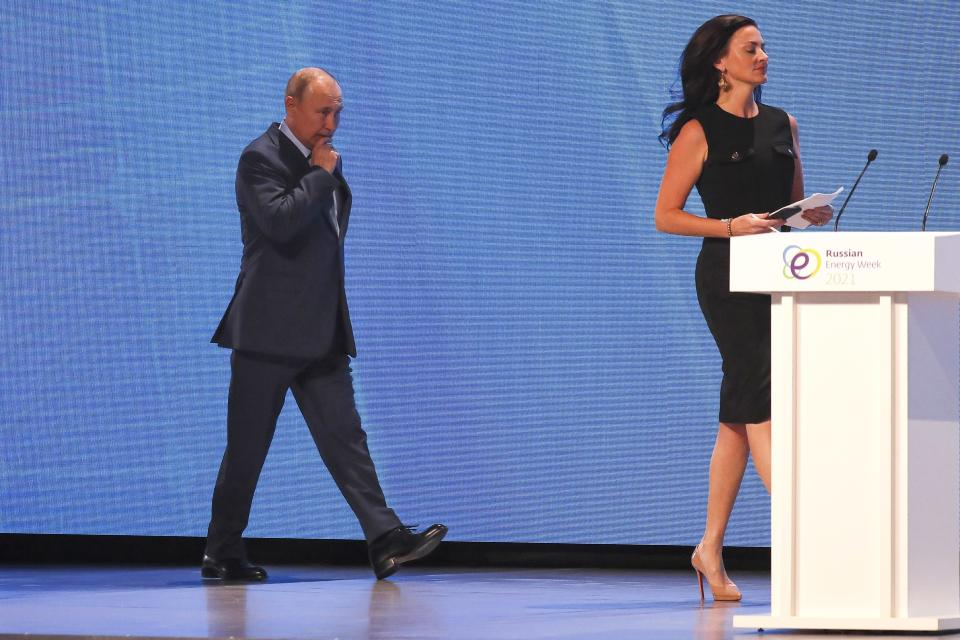 Russian President Vladimir Putin and CNBC's anchor Hadley Gamble arrive to attend the plenary session of the Russian Energy Week in Moscow, Russia, Wednesday, Oct. 13, 2021. (Sergei Ilnitsky/Pool Photo via AP)