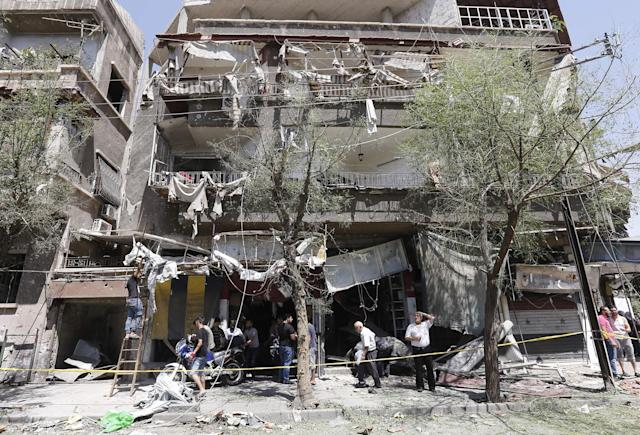 <p>TOPSHOT – Syrians inspect the damage at the site of a suicide bomb attack in the capital Damascus' eastern Tahrir Square district, on July 2, 2017. (Louai Beshara/AFP/Getty Images) </p>