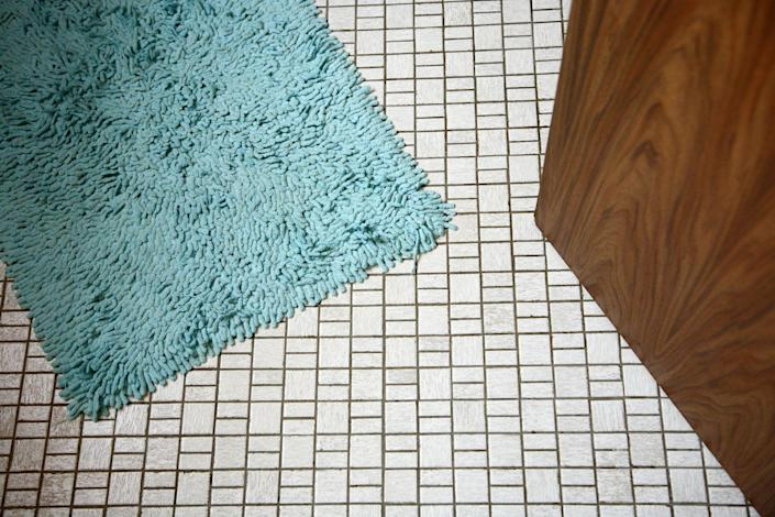 """<p>Bathroom rugs are a hot spot for mildew, bacteria, and even fungi, so they should be washed at least every two to three weeks, according to Merry Maids. Before <a href=""""https://www.merrymaids.com/cleaning-tips/quick-tips/how-to-wash-bathroom-rugs/"""" rel=""""nofollow noopener"""" target=""""_blank"""" data-ylk=""""slk:washing your bathroom rugs"""" class=""""link rapid-noclick-resp"""">washing your bathroom rugs</a>, check the manufacturer's care label to find washing instructions. Microfiber or chenille can typically be washed with a gentle laundry detergent on the cold setting and dried on the lowest heat setting. </p><p>Plastic- and rubber-backed bathmats can also usually be washed a gentle laundry detergent on the cold setting. However, you should avoid drying plastic- or rubber-backed mats with heat, as it can cause the backing to crack or even melt. </p>"""