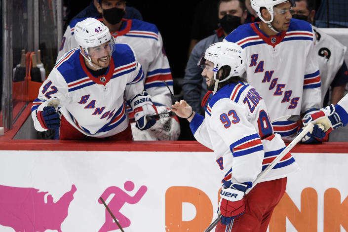 New York Rangers center Mika Zibanejad (93) celebrates his empty net goal with defenseman Brendan Smith (42) during the third period of an NHL hockey game against the Washington Capitals, Saturday, Feb. 20, 2021, in Washington. The Rangers won 4-1. (AP Photo/Nick Wass)