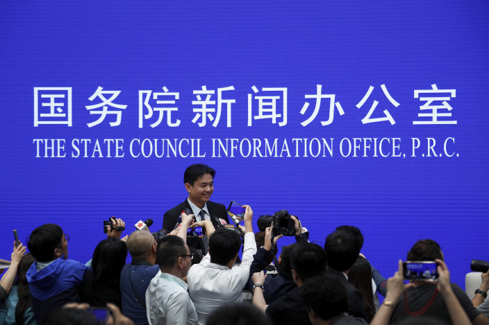 Yang Guang, spokesman of the Hong Kong and Macau Affairs Office of the State Council, is approached by reporters as he prepares to leave after a press conference about the ongoing protests in Hong Kong, at the State Council Information Office in Beijing, Monday, July 29, 2019. Yang said some Western politicians are stirring unrest in Hong Kong in hopes of creating difficulties that will impede China's overall development. (AP Photo/Andy Wong)