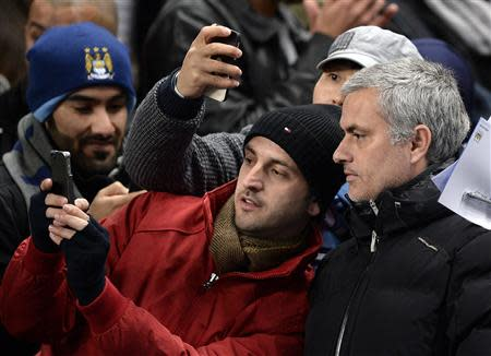 Chelsea manager Mourinho has his photograph taken with fans before their English Premier League soccer match against Manchester City at the Etihad Stadium in Manchester