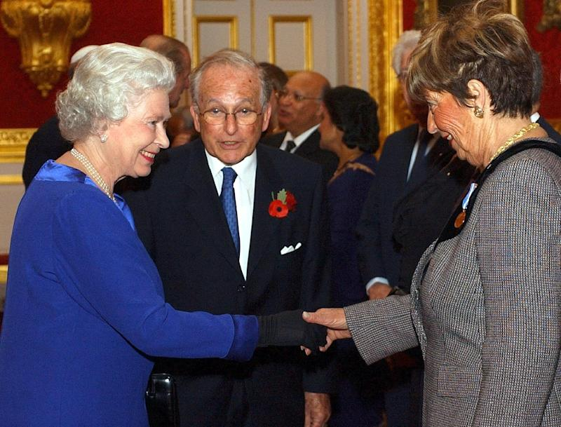 Queen Elizabeth II meets Cyril Reitman, as Lord Greville Janner (centre) looks on at a reception in London on October 29, 2003