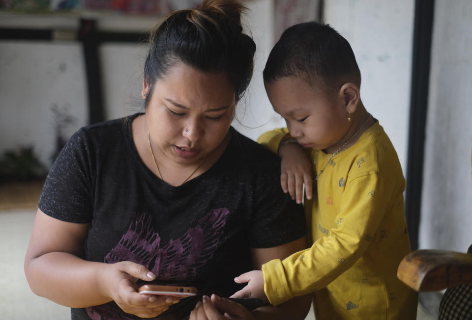 Diana Khumanthem, 30, and her three-year-old nephew Hridhaan looks at photographs on the mobile phone of Hridhaan's mother Ranjita, who died of COVID-19, at home in Imphal, in Manipur, India, Monday, June 28, 2021. Diana lost both her mother and sister to the virus in May. A public hospital treated Diana's mother, but her sister Ranjita was admitted to a private one that cost $1,300 per day. Ranjita was the family's only earner after Diana left her nursing job last year to return home during the first wave of the virus. She's now hunting for work while looking after her father and her sister's 3-year-old son. (AP Photo/Yirmiyan Arthur)