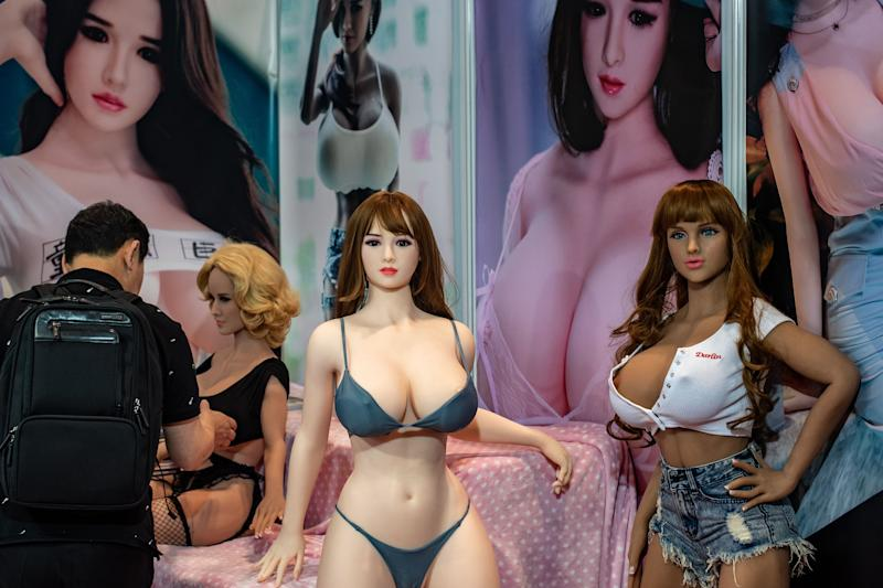 A visitor (L) checks a sex doll at a stall during the Asia Adult Expo in Hong Kong on August 29, 2018. (Photo by Philip FONG / AFP) (Photo credit should read PHILIP FONG/AFP via Getty Images)