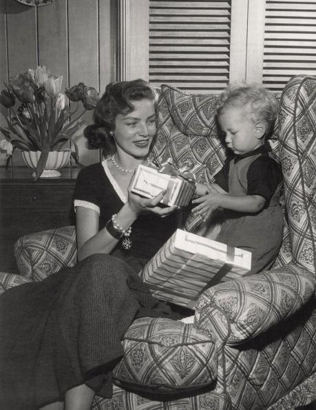 <p>Lauren helps her son Stephen open presents in her Los Angeles home with Humphrey Bogart. The couple, who married in 1945, welcomed their eldest child in 1949. </p>