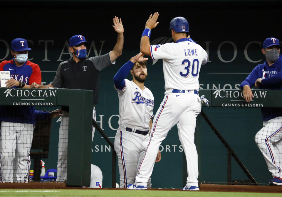 Texas Rangers' Nate Lowe, right, is greeted at the dugout by manager Chris Woodward, left, and Joey Gallo, center, after scoring against the Baltimore Orioles during the fourth inning of a baseball game in Arlington, Texas, Saturday, April 17, 2021. (AP Photo/Ray Carlin)