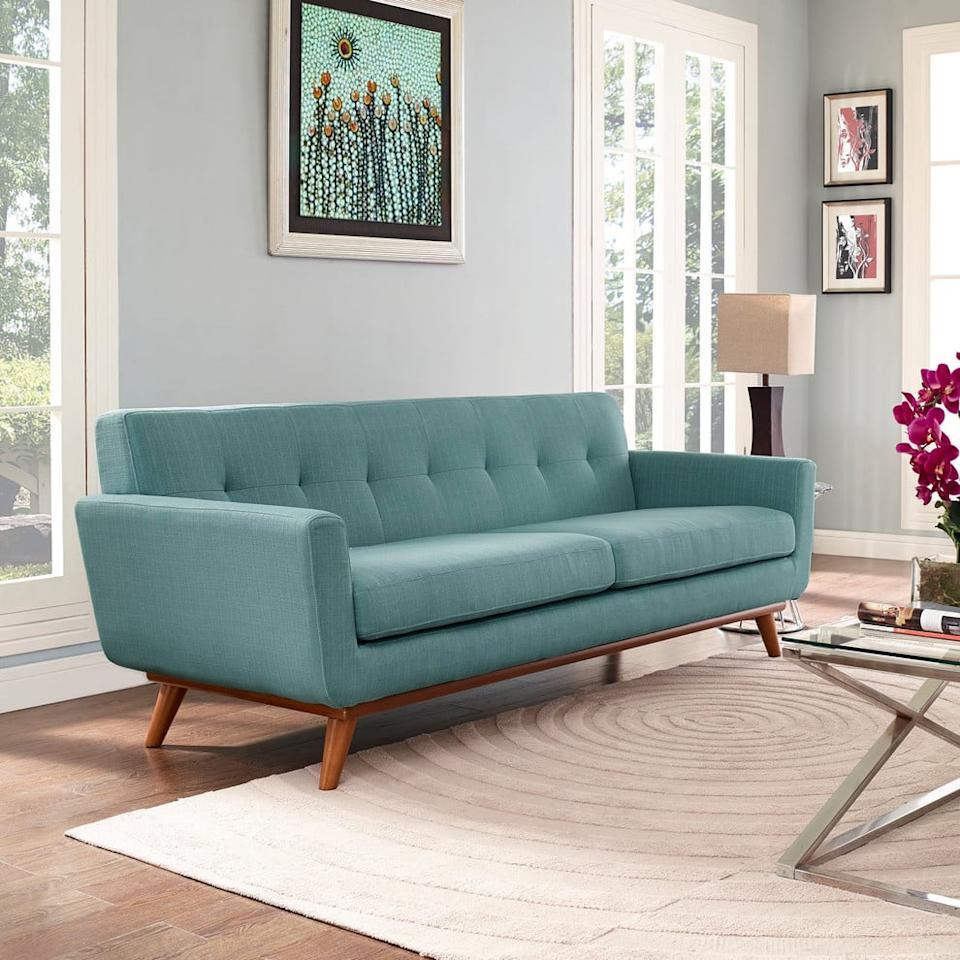 """<p>If you love mid-century designs, get this <product href=""""https://www.houzz.com/products/engage-upholstered-fabric-sofa-laguna-prvw-vr~68764481"""" target=""""_blank"""" class=""""ga-track"""" data-ga-category=""""Related"""" data-ga-label=""""https://www.houzz.com/products/engage-upholstered-fabric-sofa-laguna-prvw-vr~68764481"""" data-ga-action=""""In-Line Links"""">Modway Engage Upholstered Fabric Sofa</product> ($830, originally $1,569).</p>"""