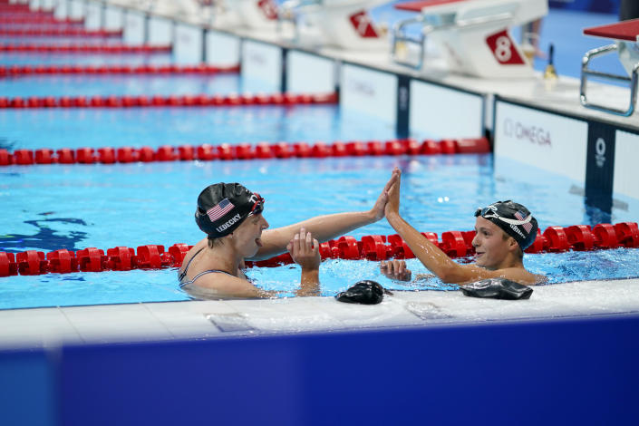 Kathleen Ledecky, of the United States, left high-fives teammate Katie Grimes after Ledecky won the women's 800-meter freestyle final at the 2020 Summer Olympics, Saturday, July 31, 2021, in Tokyo, Japan. (AP Photo/David Goldman)