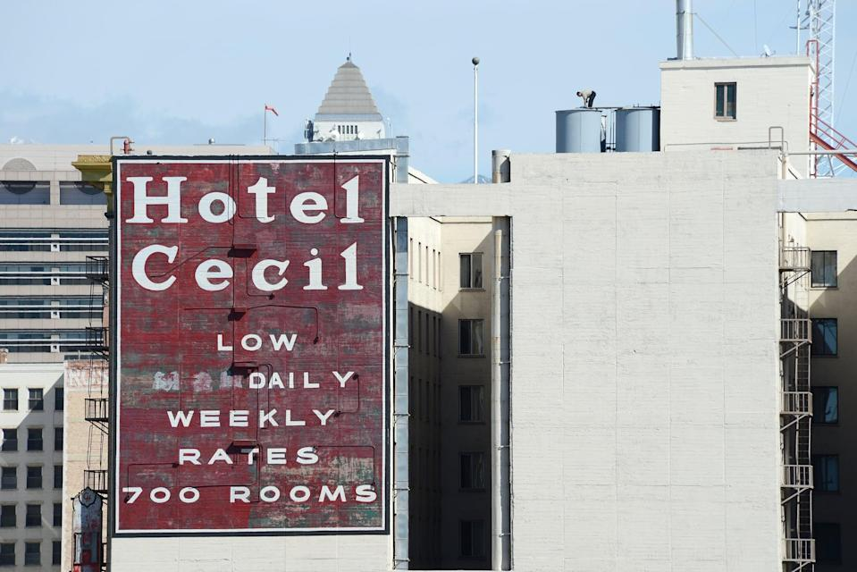 A worker stands on a water tank on the roof of the Hotel Cecil in Los Angeles California February 20, 2013. The body of 21-year-old Canadian tourist Elisa Lam was found in a water tank on the roof of the hotel three weeks after she went missing, police said. The corpse was found February 19 after hotel guests complained of low water pressure.  AFP PHOTO/Robyn BECK        (Photo credit should read ROBYN BECK/AFP via Getty Images)